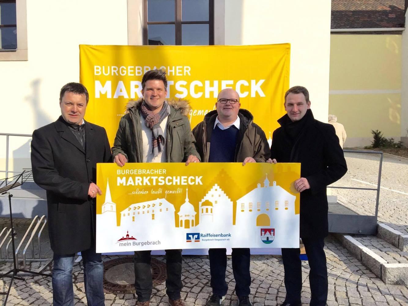 Auf dem Burgebracher Frühjahrsmarkt 2016 wurde die offizielle Einführung des Burgebracher Marktschecks gefeiert! v.l.n.r.: Peter Pfohlmann (2. Bürgermeister Markt Burgebrach), Stefan Mohr (Projektleiter meinBurgebrach.de), Markus Dürrbeck (Vertreter Raiffeisenbank Burgebrach-Stegaurach) und Johannes Maciejonczyk (1. Bürgermeister, Markt Burgebrach).